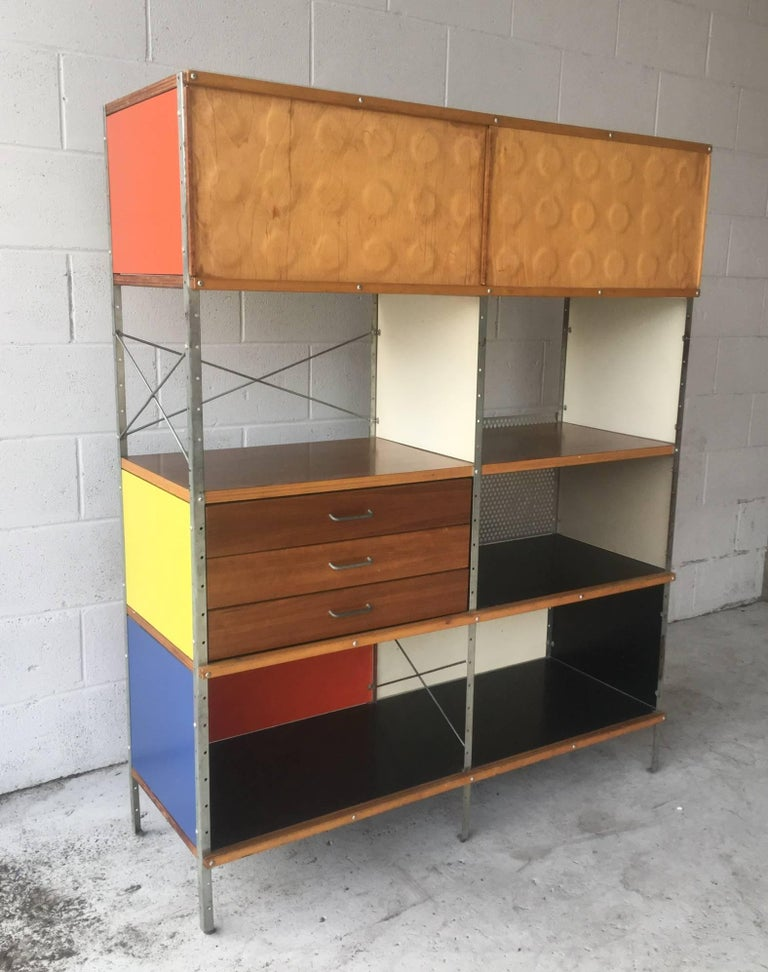 The holy grail for Eames collectors. This marvellous ESU is from the first generation. Features walnut veneer and primarily colored panels, the most sought after combination. Also features two birch dimple doors for top section. Drawers function