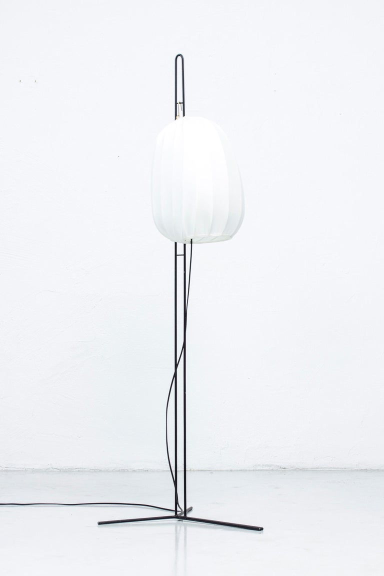 Rare floor lamp designed by Hans Bergström. Produced by his company Ateljé Lyktan in Åhus Sweden, during the early 1950s. Designed, at the latest, 1950. Made from black lacquered metal and shade with chintz fabric in off white. Small brass detail