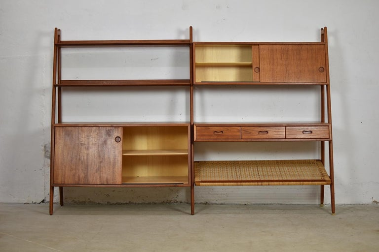 Proud to present you this rare freestanding bookshelf designed by Arne Vodder & Anton Borg for Vamo, Denmark, 1950s. This bookcase features several shelves, cabinets and a rattan magazine holder, all in teak. Freestanding because of the finished
