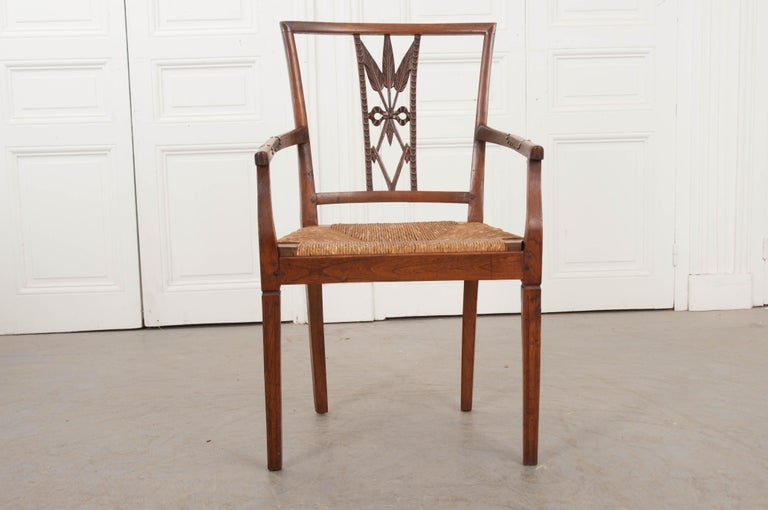 """This remarkable and rare Louis XVI-style walnut armchair, circa 1850, is from the provincial countryside of France and features a unique """"wheat-sheaves-and-diamond"""" chair back design over a fantastic removable rush seats and supported on delicate"""