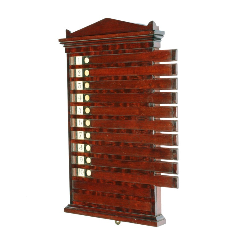 A rare early 19th century George IV mahogany 'Life Pool' scoreboard.  The board comprises 12 sliding mahogany strips which expose a number and three circular markers.  Each player (up to 12) would have three lives and as they lost a life the