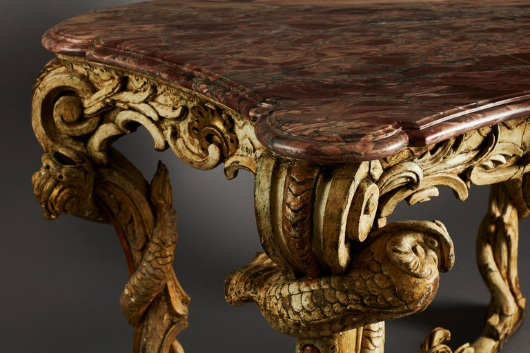 A very unusual and superb Rococo console table from the mid-18th century. On four carved legs with an X-shaped stretcher, overall with scrolls and dolphin-like sea creatures. This extravagant console table recalls features of fantastic 18th century