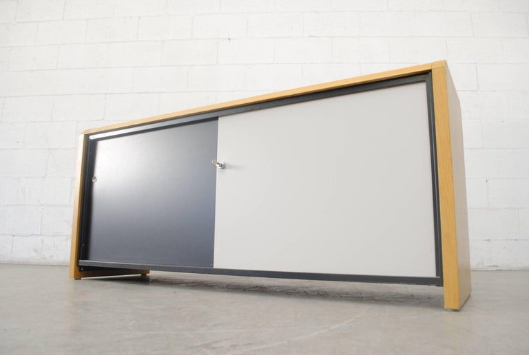 Rare midcentury credenza for Gispen with two enameled metal sliding doors in black and light-grey. Key lock on grey door. One metal shelf inside. Blonde wood frame with black enameled metal back. Gispen label on top-left as pictured. Amazing piece!