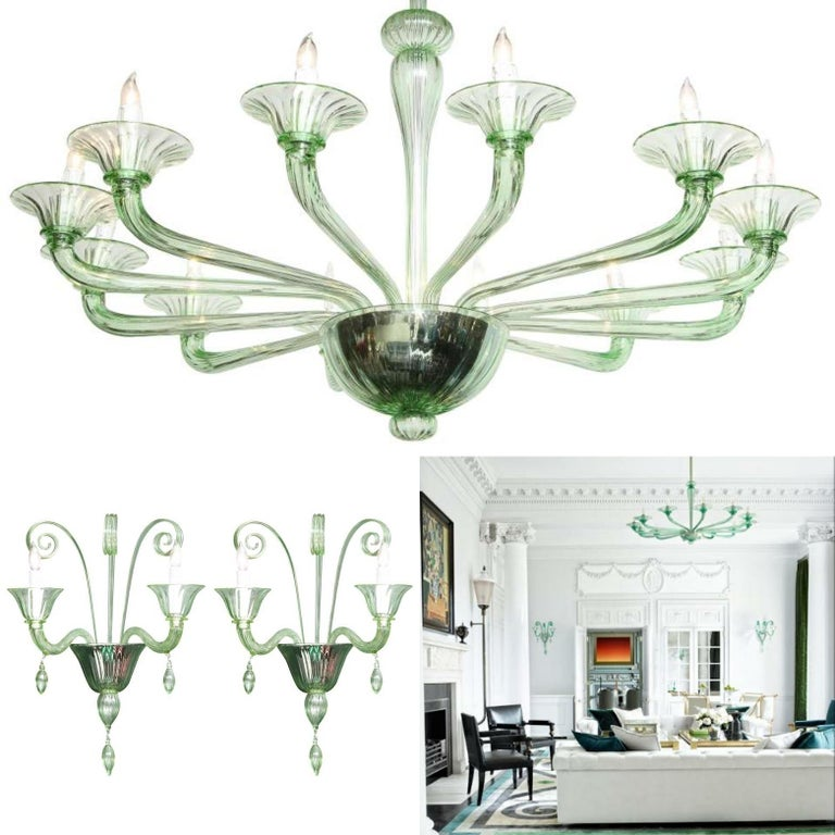 A classic chandelier of midcentury beauty in a rare green Murano glass in the spirit of Venini. Translucent green Murano glass chandelier with 12 arms and fluted glass cups. 12 light bulb sockets. Height including chain and matching glass canopy is