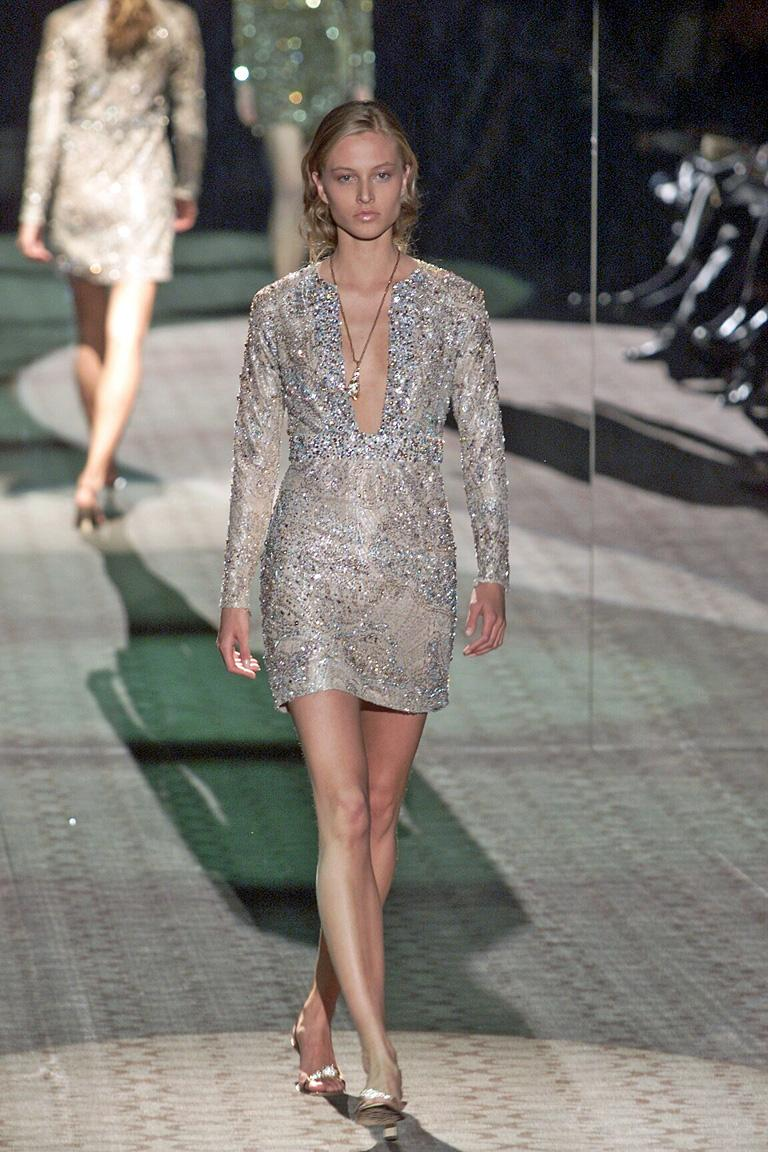 A rare Gucci Tom Ford 2000 Runway evening dress.  Fashioned of champagne lace with a hint of silver.  Embellished with hand sewn multi-size pink, blue and clear crystals  Rare: not many of these dresses were produced.  An exceptional piece.  Dress