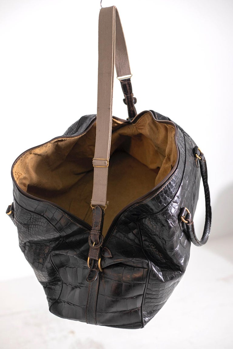 Rare and beautiful Gucci travel bag from 1960's embossed crocodile leather with large chocolate brown flakes. With adjustable fabric shoulder strap, hard leather handles and a large double zipper throughout the bag. It has a gold aged metal