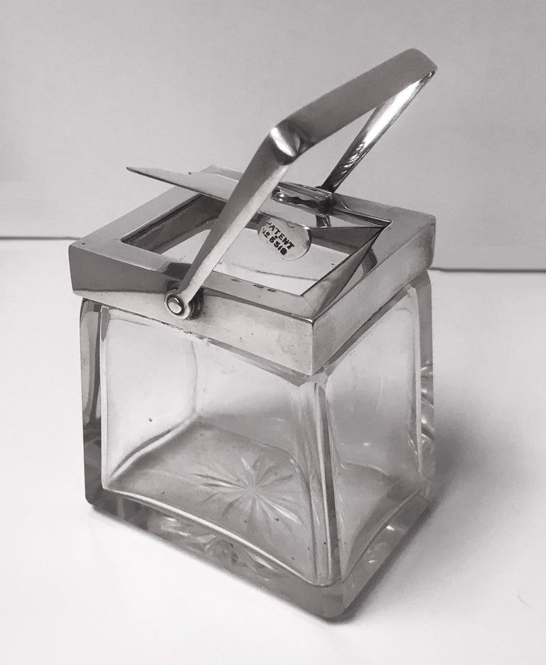 Very rare Heath and Middleton (Hukin and Heath) glass and silver mechanical condiment jar, Birmingham, 1906. Full hallmarks to handle, mount and cover and design No 18226 and Patent No 5518. Hinged cover fitted with unique mechanical handle which