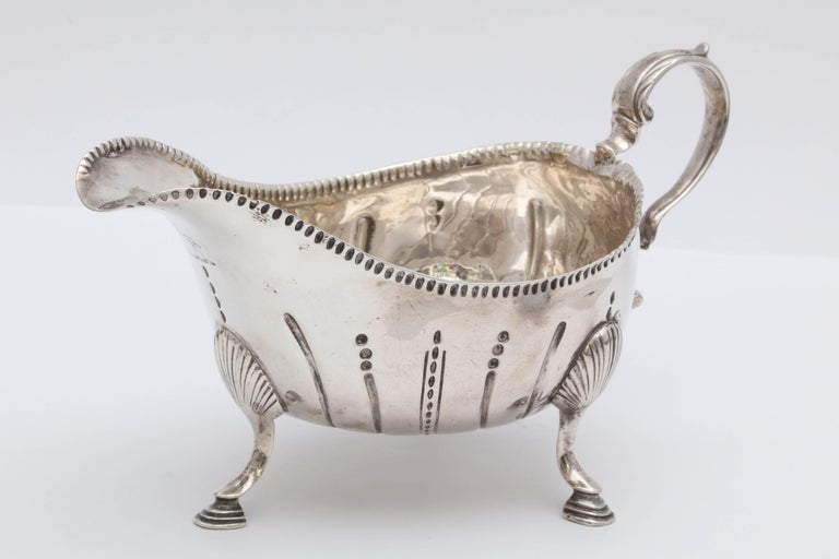 Beautiful and rare Irish, George III, Sterling silver footed sauce/gravy boat, Dublin, 1771, John Lloyd - maker. Graceful design. Lightly gilded inside. Measures 6 1/2 inches from edge of handle to edge of spout x 3 3/4 inches high (to top of