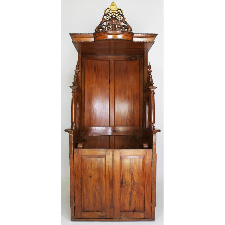A rare Italian 19th century carved pine Catholic Church confessional stall, booth. The Baroque revival body crowned with a carved and parcel gilt Papal insignia, the official decoration for the Pope in his capacity as the head of the Roman Catholic