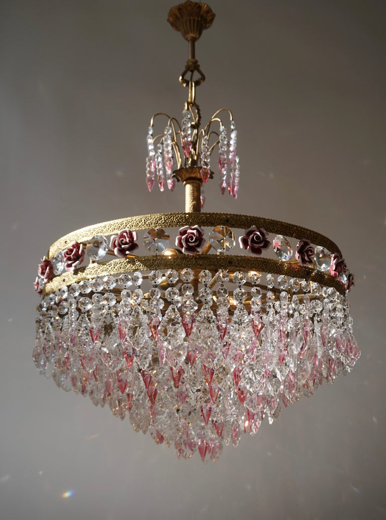 Elegante Italian brass chandelier with pink crystals and pink porcelain flowers.  The light requires seven single E14 screw fit lightbulbs (40Watt max.) LED compatible.  Measures: Diameter 61 cm. Height fixture 75 cm. Total height 95 cm.