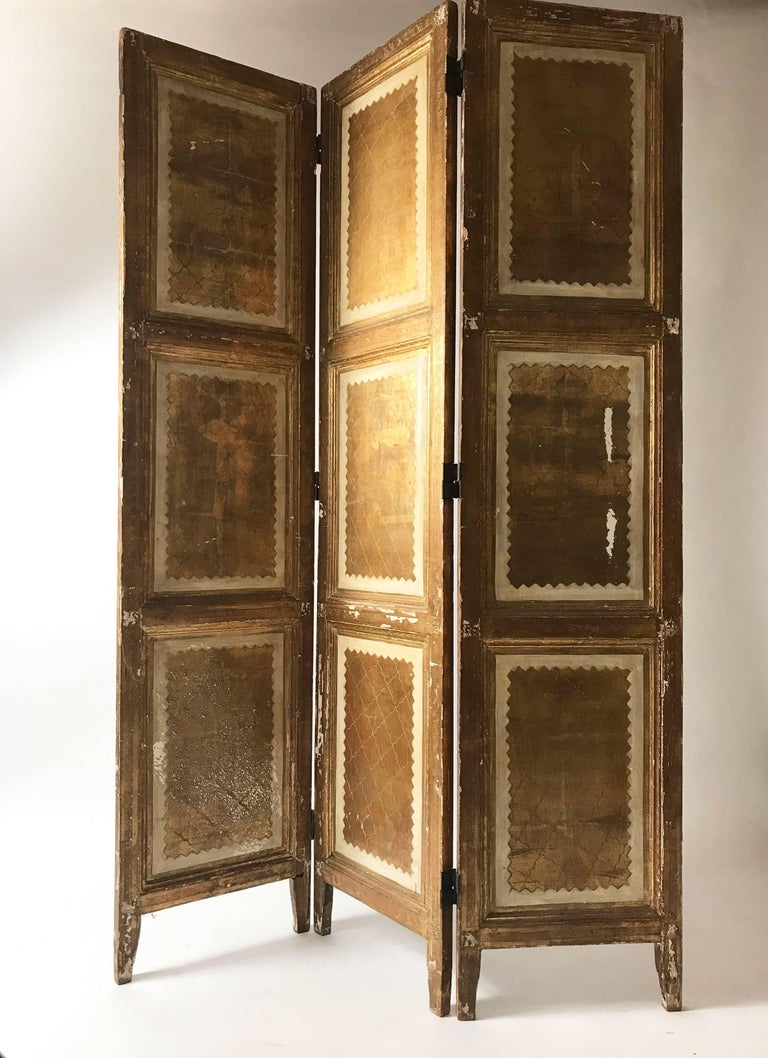 A very special Italian Florentine room divider or dressing screen. Gilded laurel motifs on a cream background. Significant wear to one of the panels but in general the patina only adds to the vintage feel. Three panels. Made in Italy.