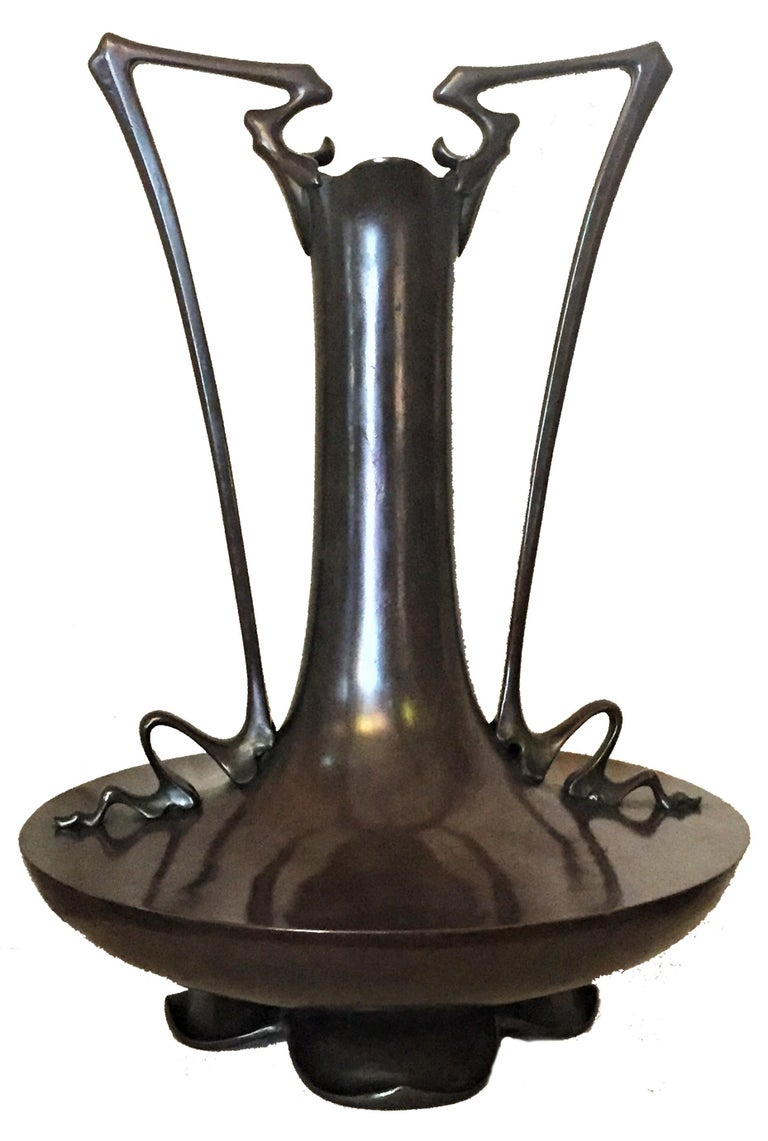 Although unmarked, this rare and important, grand but at the same exquisite patinated bronze vase has just a very few little details, defying the shape of the handles, as well as the base, depicting an overturned lotus flower; clearly suggesting the
