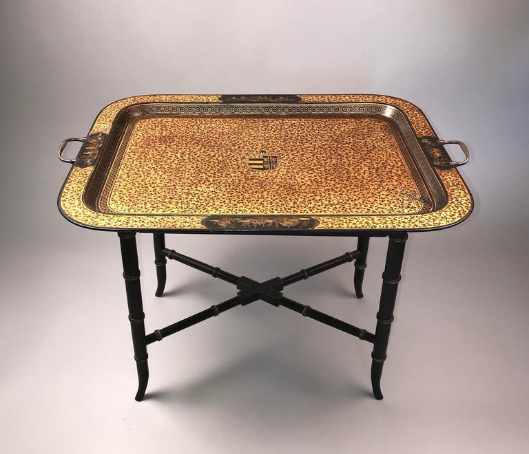 A rare japanned tray table. English Regency period.  Early 19th century, ca 1810.  The dished top exquisitely decorated overall with complex floral designs in gilt, and unusually centred by an armorial. The raised borders have very finely executed