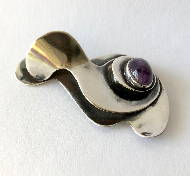 An early multi layered sterling silver and amethyst brooch designed by Joan Hurst and Jill Kingsbury of New York City, New York.  This is a large example of their work and has surrealist influence as seen in works by Sam Kramer. The brooch measures