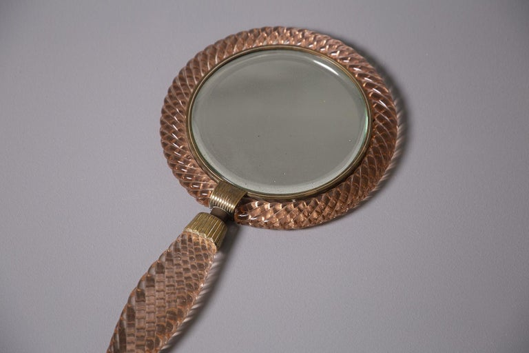 Rare and magnificent ladies' toilet mirror designed by Venini from 1939, Italy. The women's mirror is made in press or rather braided in antique pink Murano glass. Inside there is an antique circular mirror. Its connecting elements are in worked