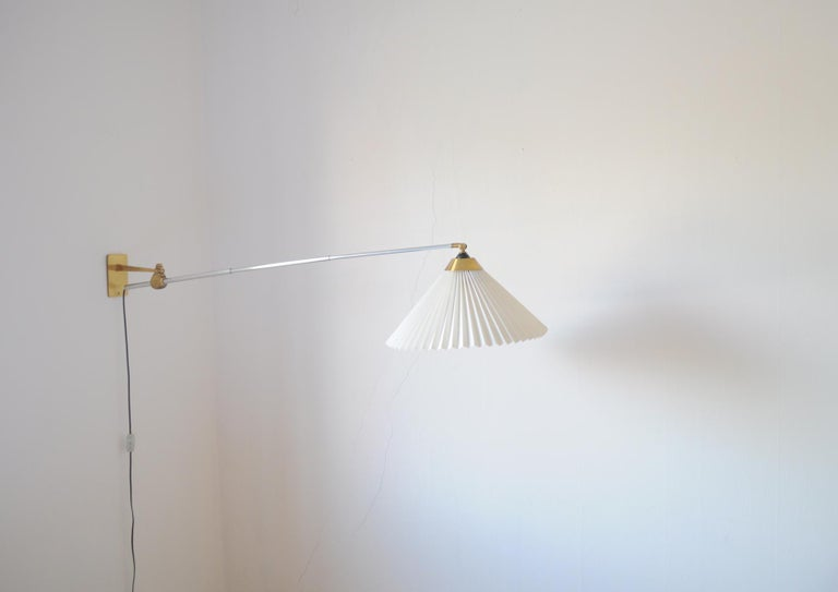 Rare wall lamp with three-piece telescopic metal arm. Swivel and wall mount made in brass, mounted with original pleated Le Klint screen, suspension brackets included.  Designed in 1963 by Peter Hvidt & Orla Mølgaard-Nielsen.  Produced by Le