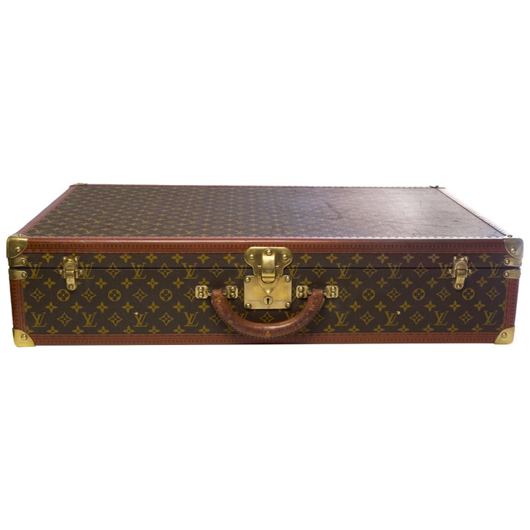Beautiful decorative and collectible object:  Lovely Louis Vuitton Alzer 80 suitcase in monogram canvas and brown lozine, brass trim, natural leather handle allowing a handheld.  Three brass clasps. Lining in beige canvas, two straps to hold