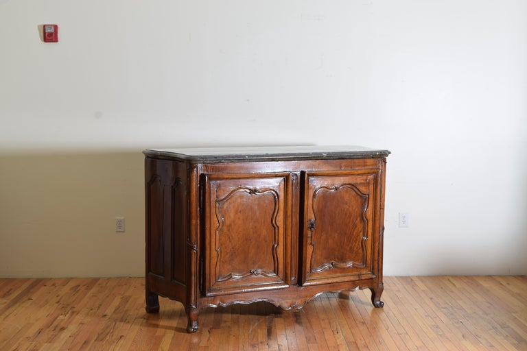 Rare Louis XIV/XV period carved walnut buffet, Marrone fossilized marble top having a thick shaped Maronne Fossil marble top atop a conforming case with stylized carved door panels and rounded corners with carved feet and apron, the interior and
