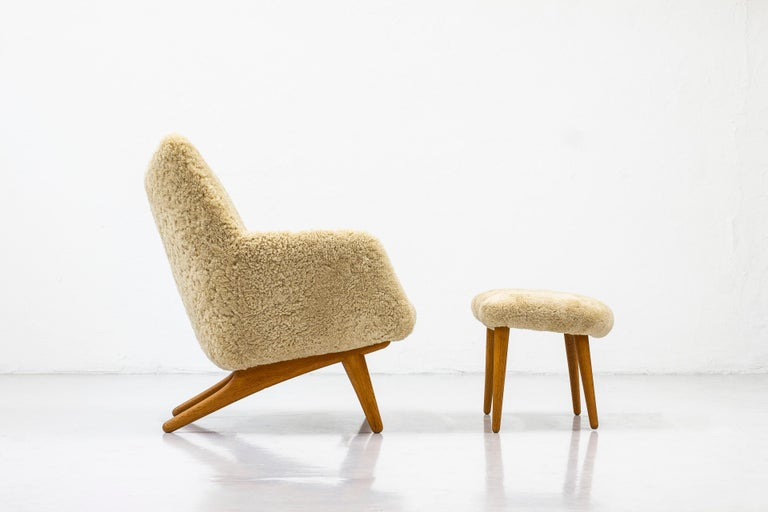 Rare lounge chair with ottoman designed by Illum Wikkelsø. Produced in Denmark by cabinet maker Mikael Laursen. Solid oak legs. New padding and upholstery in beige sheep skin. Excellent vintage condition with hardly any wear, restored.