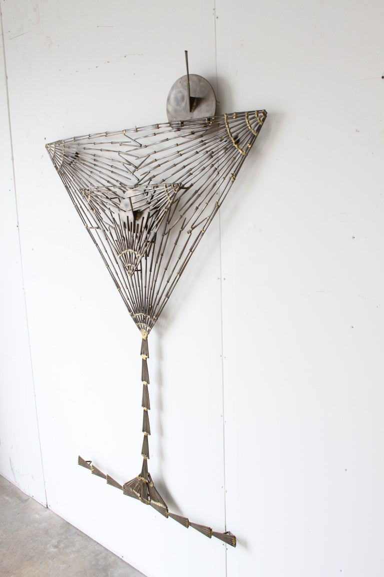Very unique wall sculpture of a large martini glass with olives and ice made of nails in the Brutalist style by St. Louis artist Marc Weinstein, possibly a commission for a bar. Overall very nice condition, light patina, no breaks or loss. Marc