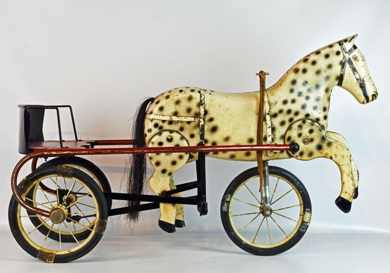 This sulky style pedal tricycle features a seat supported by two wheels and an intriguing tole horse mounted on the front wheel in a way that lets the horse legs move as the tricycle moves forward.
