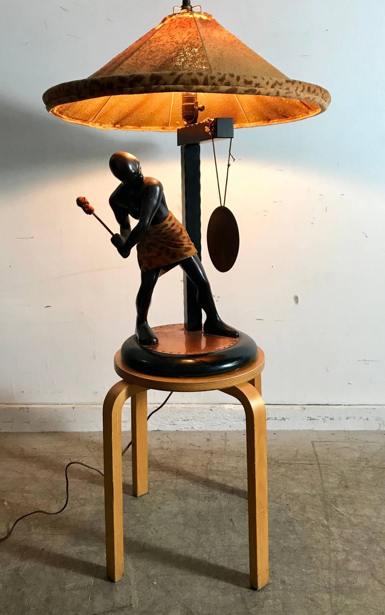 Stunning depiction of strong Nubian figure striking gong, bronzed clad plaster figure, retains original mallet as well as original lampshade, both in need of some repair ,wood and copper disk base, brass hanging gong.