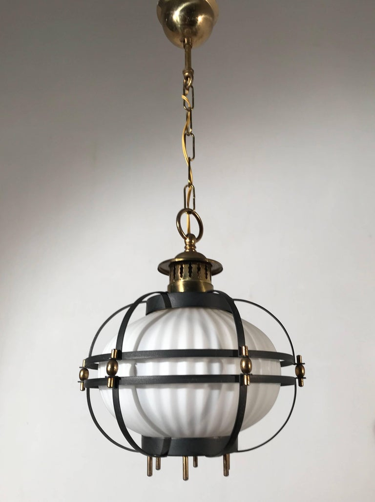 Stylized maritime pendant with a modern twist.  The basic design underneath this Mid-Century Modern light fixture is that of a ships lantern. The cage would protect both the sailors and the glass shade inside. The earliest ships lanterns were much