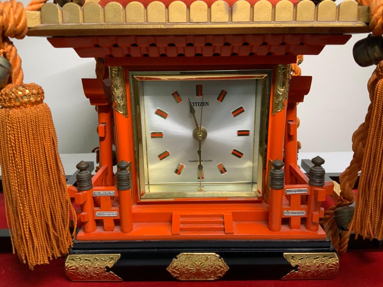 This is a square Citizen clock mounted in a shaped Mikoshi Palanquin-Shinto Shrine wood (This is a vehicle that the Japanese people used to transport a deity during festivals). The Mikoshi is hand painted orange with gold details. There is a large