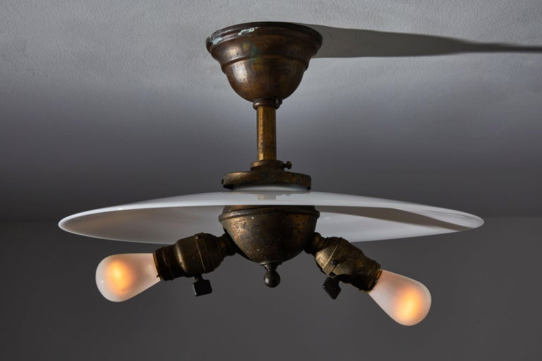 Rare industrial milk glass flushmount ceiling light. Designed and manufactured in the United States in the early 1900s milk glass, with all original patinated brass hardware and two way bulb cluster with original turn keys on sockets. Original brass