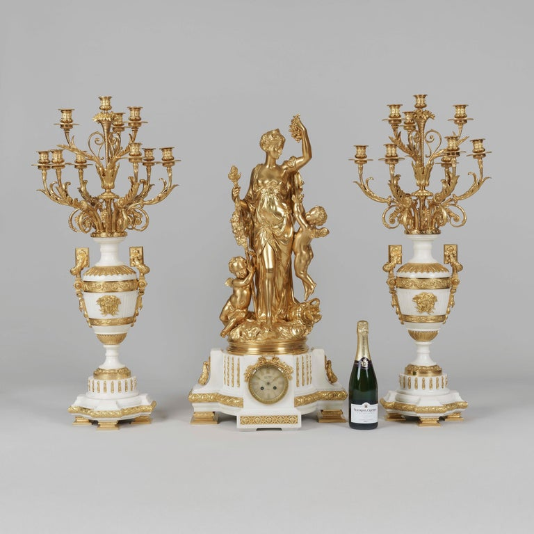 An Exhibition Quality Garniture de Cheminée By Jules Graux of Paris  Of important size and supreme quality, the mantle clock constructed from white Carrara marble, rising from ormolu supports and decorated with laurel wreaths, guilloches, and a