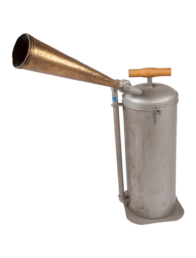 A rare ship's horn made of iron from a decommissioned ship. It is in working order. The top plunger with a wooden handle lifts and when pushed down, the Horn sounds. The flared horn or trumpet transfers the sound to the open air and can be moved so