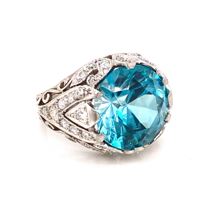 Gorgeous Natural Blue Zircon gemstone set in a hand crafted diamond mounting. The 11.74 carat round blue zircon has not had any heat or color treatment. AGL certificate included. The zircon measures 13.4 x13.2mm, and is set in a beautiful handmade
