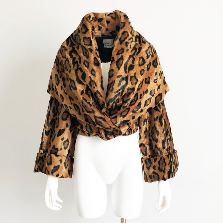 Vintage Norma Kamali Cropped Leopard Jacket with Shawl Collar, circa the 1980s.  Huge shawl collar can be worn many ways, as we show in our images.  Fastens with two fur-covered buttons. Fully- lined/shoulder pads/dry-clean only.  Made from faux fur