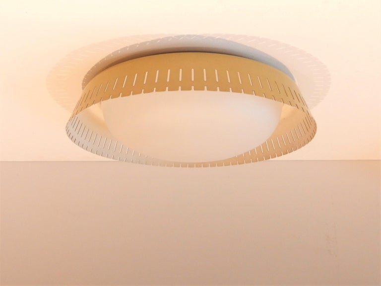 This ceiling lamp was designed by Bent Karlby in Denmark in the 1960s. A lamp that is not often seen. It is made of satin opaline glass surrounded by a yellow perforated metal edge that gives a beautiful and soft illumination. It has has 2 screw