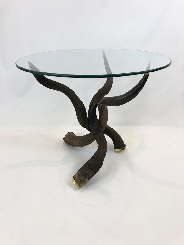 A sculptural custom made tripod coffee table having 3 kudo horns elegantly arranged with tips at the top perfectly poised to hold the brand new bevelled round piece of glass. The ends of the horns on the floor terminate in brass caps. Base is 21 W