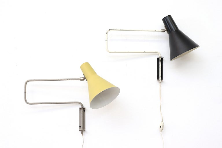 Rare Anvia midcentury wall lamp with extendable 'paper clip' arm, tubular white enameled metal frame paired with swivelling black shade create a versatile classic look. In original condition with visible wear and enamel loss. Also available in pale