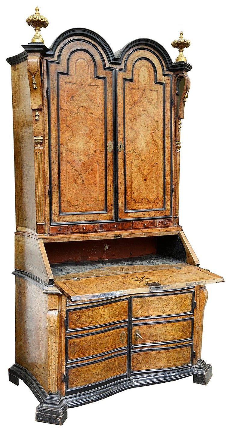 A rare and impressive pair of 18th century Italian burr walnut double dome bureau bookcases, each with canted corners, turned, carved and gilded finials. Ebonised moldings, panelled doors with burr walnut veneers, inlaid shaped panels to the doors,