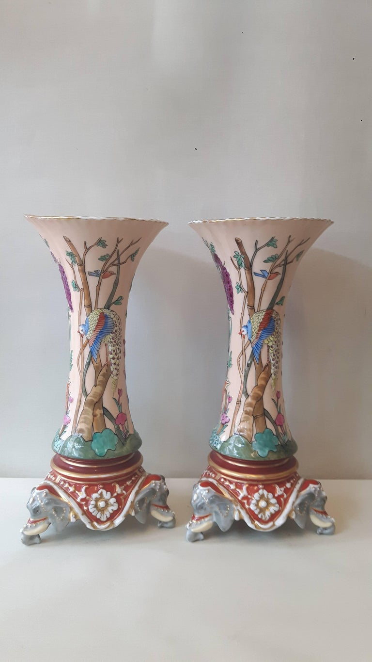 An extremely unusual pair of Paris porcelain trumpet-shaped vases in the C18 Mogul Indian style, hand-decorated with exotic birds in trees and foliage, the body sitting on porcelain elephant heads,