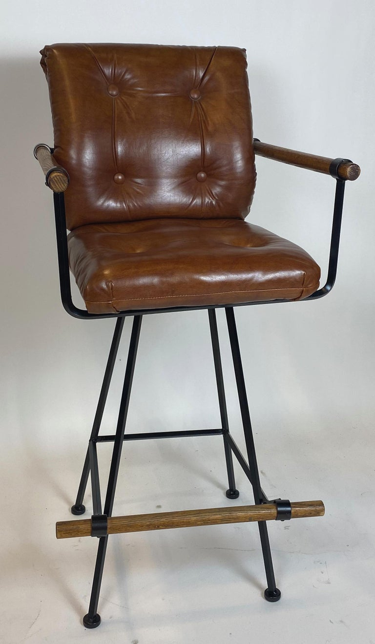 Rarely seen pair of barstools with arms by Cleo Baldon. The solid steel frames have been freshly repainted in satin black as original. The oak accents are in original condition. Upholstery is worn and in need of replacement. Feet are fitted with new