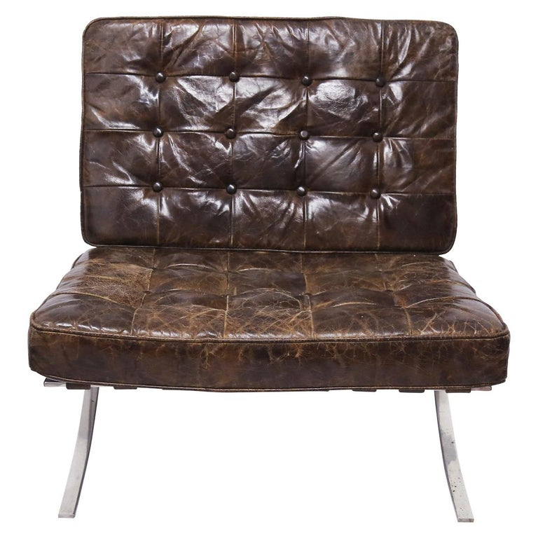 Elegant pair of Mies van der Rohe Barcelona chairs. The chairs are upholstered in brown leather that has a an exquisite patina.