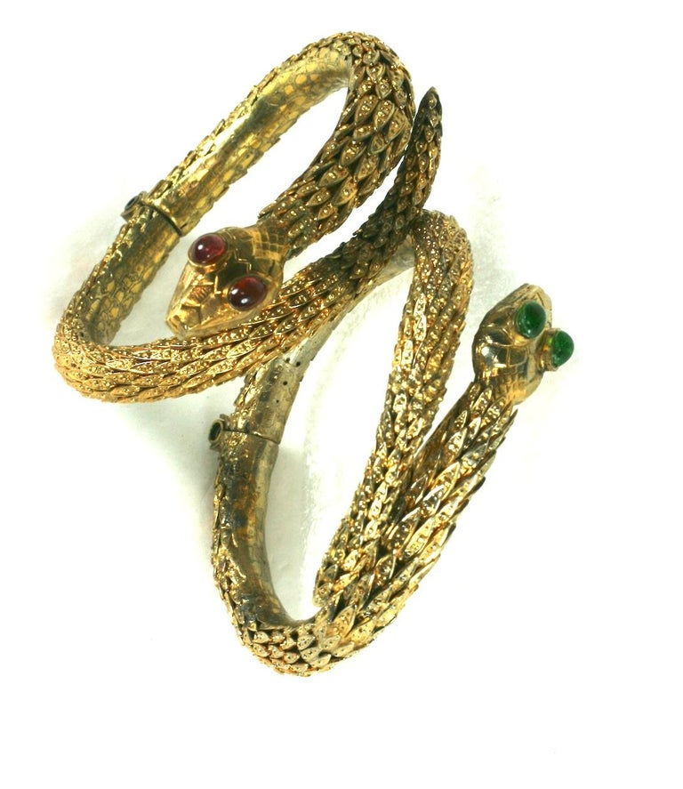 Rare Pair of Period Haute Couture Chanel Snake Bangles by Maison Goossens. These hand made hinged bracelets are composed of dozens of graduated gilt filigree caps soldered together to form the body of each bracelet. Each snake head is hand made with