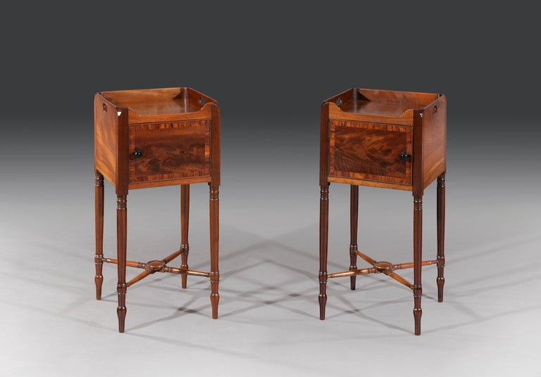 The square tops have a wraparound galleries with cut-out carrying handles. The flamed doors are opposite opening with finely turned ebony handles. The bedside cabinets stand on elegant turned legs with cross stretcher. Original through-out.