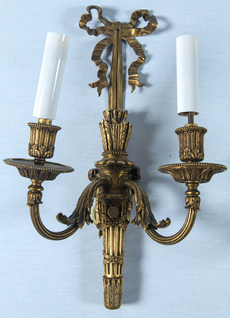 A rare pair of gilt bronze circa 1900 E F Caldwell sconces. Made in the French Louis XVI iconic style with high quality crisp casting and rich gilt bronze patina now nicely tarnished and aged. Original mark of C with diamond border stamped on back
