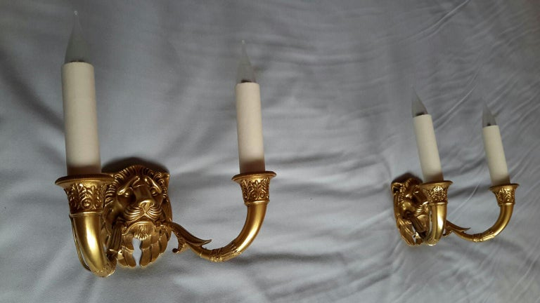 Rare and beautiful pair of double sconces French Empire style from beginning of the 20th century in gilted bronze figuring lion's head. The sconces are in magnificent condition. Electrical parts have been renewed with hard cardboard sleeves in