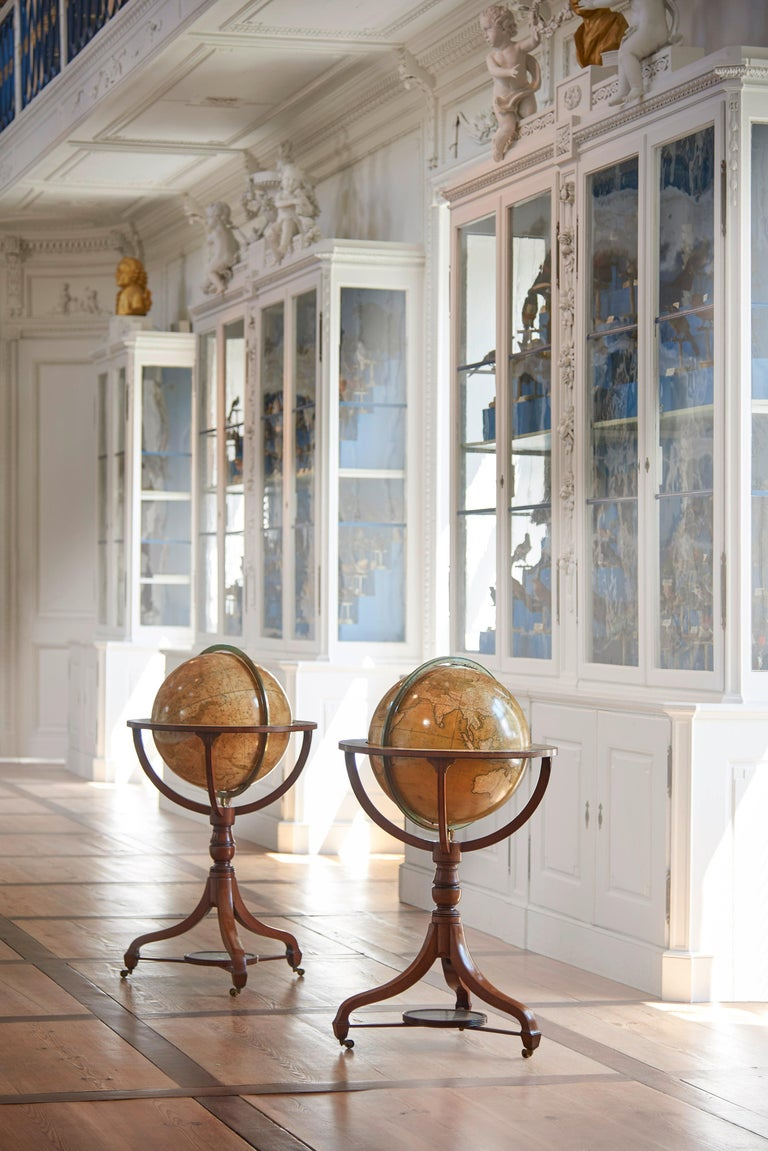 London, 1816/1828 Colored and lacquered copper engravings, three-legged mahogany mounts and each with a compass. Both globes have an equatorial ring with month indications and a brass meridian ring with indication of the polar altitude. Both