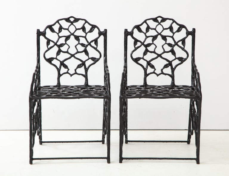 Rare pair of petite JW Fiske cast iron garden chairs.