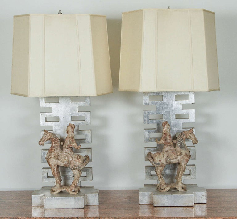 Gorgeous pair of table lamps by James Mont. They have silver leafed oriental style pedestals that support polychromed wooden figurines of equestrian Chinese warriors. The one sided fabric shades are original.