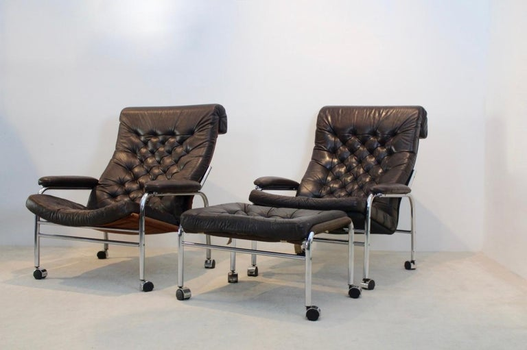 An extremely rare and beautiful pair of 1970s original Noboru Nakamura leather button back lounge chairs, with a matching footstool in chocolate brown leather. The 'Bore' called chairs and stool have a light chrome tubular frame with removable