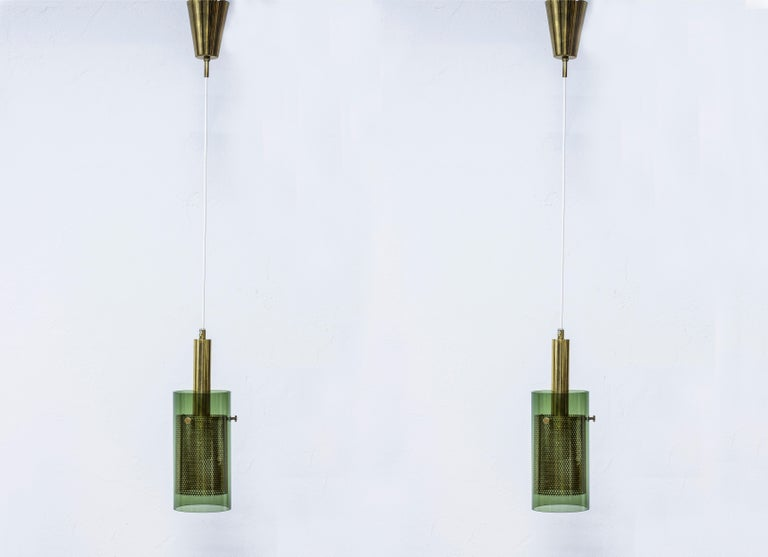 Pendant lamps designed by Hans Agne Jakobsson during the 1960s. Produced by his own company in Markaryd, Sweden. Made from polished brass with hand blown green glass shades and perforated brass diffusers. With original ceiling mount in brass.