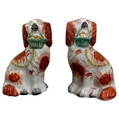 Rare Pair of Staffordshire Seated Red Spaniels with Baskets of Flowers